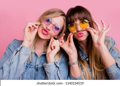 Blonde woman fooling  around with  her  best friend . Two sisters having fun  and making grimace over pink background.