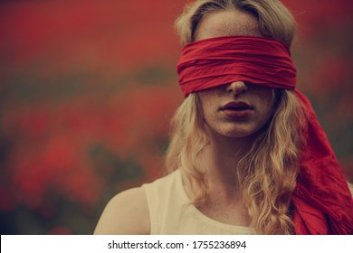 blonde woman with freckles wearing red scarf as blindfold