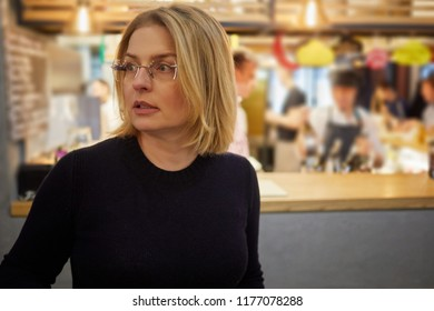 Blonde woman in glasses stands in cafe with her back to bar counter.