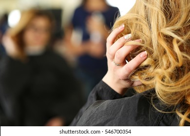 Blonde woman at hairdresser checking and fixing her new curly hairdo with hand. Keratin restoration, latest trend, fresh idea, haircut picking, shorten tips, instrument store concept