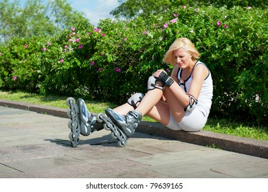 Blonde woman has hit a knee skating on roller-skaters and it hurts