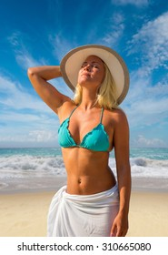 Blonde woman in hat on the beach