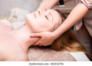 Blonde woman having facial massage in spa salon. closeup