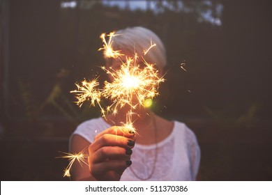 Blonde woman having fun with a sparkler.