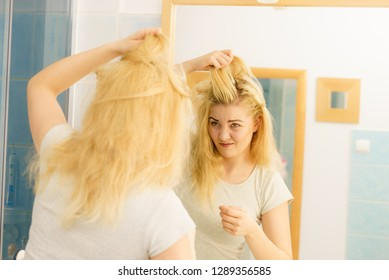 Blonde woman having problems with greasy oily hair looking at herself in bathroom. Female showing scalp, scratching herself, dandruff problem.