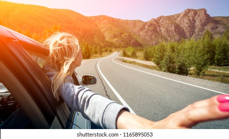 A blonde woman with her head out the window enjoying a scenic drive through the sawtooth mountain. Sun is shining. Shoot from the back
