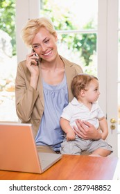 Blonde woman with his son using phone and laptop in the office