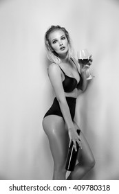 Blonde woman holding glass of wine. Beautiful female model. Hot lady in black lingerie. Fashion studio shot. Slim girl. After party. Black and white.