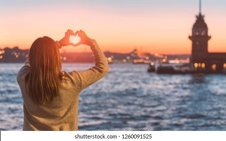 Blonde woman holding hands as heart shape with beautiful sky in warm color twilight sunset and sea background on view of Maiden's Tower. Maiden's tower (Kiz Kulesi) is one of the symbols of Istanbul.
