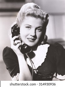 Blonde woman holding telephone receiver