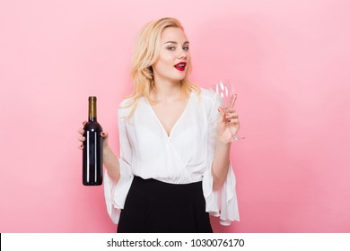 Blonde woman holding wine bottle and glass