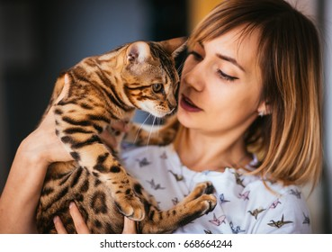 Blonde woman holds a Bengal cat