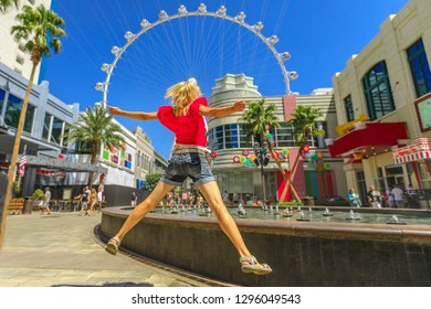 Blonde woman jumping at center of Las Vegas in a sunny day, blue sky. Ferris Wheel, the world's largest observation wheel on blurred background. Happy tourist in Las Vegas cityscape, Nevada, USA.