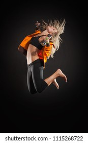 Blonde Woman Jumping with Dumbbells Isolated on Black Background