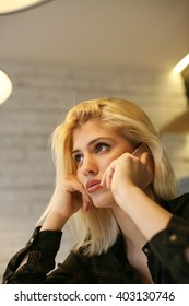 Blonde woman just listen bed news on mobile phone.