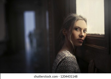 Blonde woman leaning against a door with a sad expression.