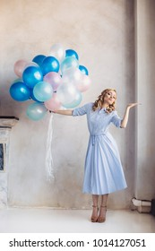 Blonde woman in light blue dress with blue and pink baloons stay and send air kiss in front of light wall