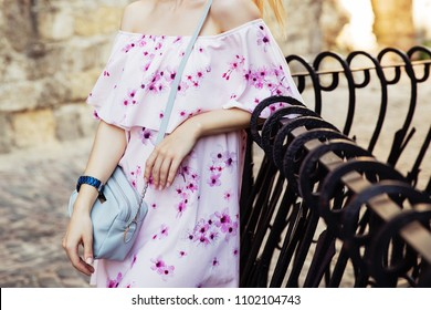 Blonde woman in light pink trendy dress with flowers and light blue leather handbag. Fashionista walking on the city street, fall street fashion look, modern outfit. Girl in dress