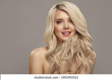Femme blonde aux longs cheveux bouclés, studio tourné sur beige isolé avec espace libre pour copie.