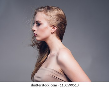 Blonde woman with long curly hair with lashes and earrings over gray background female model portrait