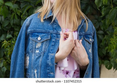 Blonde woman with long hair in ragged denim jacket  and light pink dress. Stylish street fashion look, denim outfit.