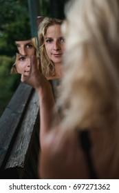 Blonde woman looking into broken mirror.