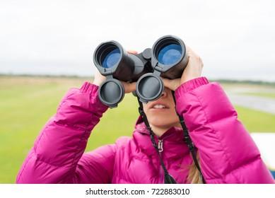 blonde woman looks in binocular
