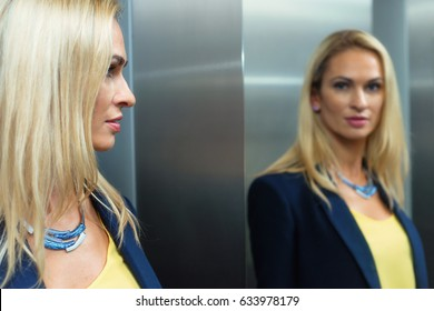Blonde woman looks in the mirror in the elevator