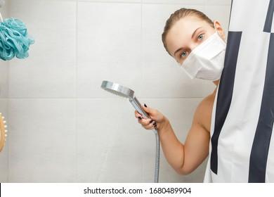 Blonde Frau in medizinischer Maske, die neben gestreiftem Vorhang in Dusche steht