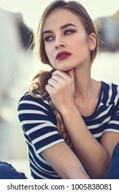 Blonde woman, model of fashion, sitting on a bench in urban background. Beautiful young girl wearing striped t-shirt and blue jeans in the street. Pretty russian female with pigtail.