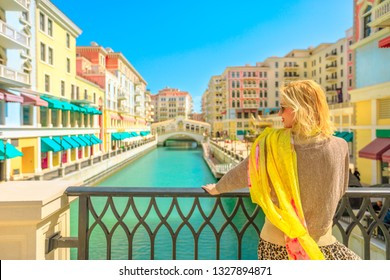 Blonde woman on balcony looking canals of Venice, a Venetian style waterfront village in sunny day. Caucasian tourist enjoys Qanat Quartier in the Pearl-Qatar, icon of Doha, Persian Gulf, Middle East.