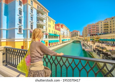Blonde woman on balcony looking canals of Venice in Doha Qatar. Caucasian tourist enjoys Qanat Quartier in the Pearl-Qatar, Persian Gulf, Middle East, Persian Gulf. Sunny day with blue sky.