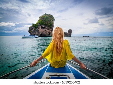 Blonde woman on the edge of a boat overlooking the ocean.