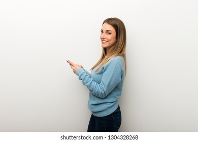 Blonde woman on isolated white background sending a message with the mobile