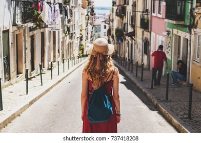 Blonde woman on trip walking by the beautiful southern streets in summer with people in background