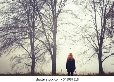Blonde woman on walk.Autumn wood. Fog background. Quiet landscape.The photo is tinted.