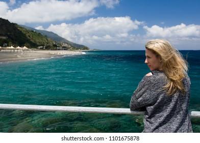 Blonde woman outdoor, azure blue sea background, beach and mountan