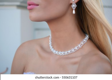 Blonde woman with pearl necklace and earrings