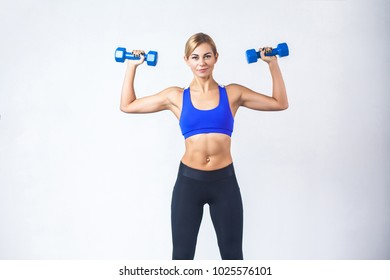 Blonde woman with perfect body, holding two blue dumbbells. Studio shot