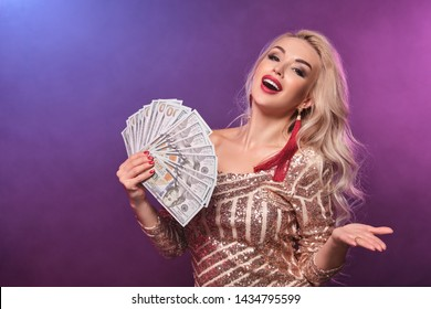 Blonde woman with a perfect hairstyle and bright make-up is posing with fan of hundred dollar bills in her hands. Casino, poker.