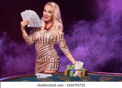 Blonde woman with a perfect hairstyle and bright make-up is posing with playing cards in her hands. Casino, poker.