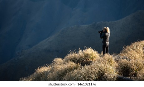 A blonde woman photographer taking pictures with DSLR camera