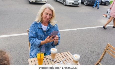 A blonde woman photographs coffee with a cell phone in a street cafe. The woman is wearing a fashionable denim jacket