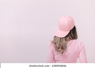 blonde woman in pink t-shirt and pink cap on light background. femininity and spring. copy space.