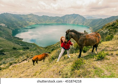 Blonde Woman Playing With Two Horses In The Lake Quilotoa, Ecuador