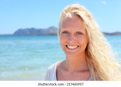 Blonde woman portrait outdoors on beach. Beautiful candid blond female model smiling happy and fresh looking at camera with lovely smile. Girl in her 20s.