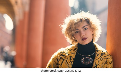Blonde woman portrait outdoors in Piazza Santo Stefano, Bologna, Italy. Natual flare.