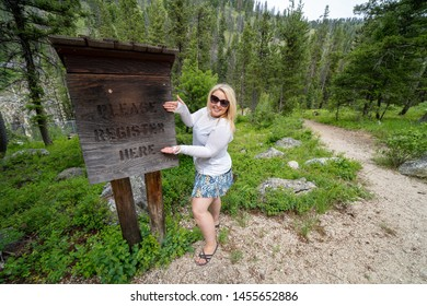 Blonde woman poses near a sign for campers and hikers to register - Please Register Here - at a campground in the Sawtooth Wilderness  National Forest in Idaho