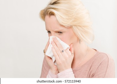 Blonde woman pressing a clean wipe on her nose as if she has sneezed with copy space