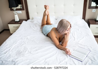 Blonde woman read book in her bed at home